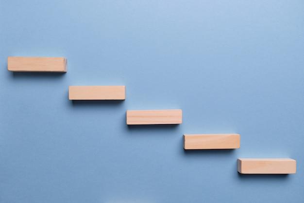 Conceito de estágios de desenvolvimento de negócios. blocos de madeira em um espaço azul.