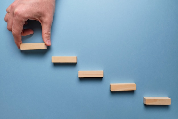 Conceito de estágios de desenvolvimento de negócios. mão segura blocos de madeira em um espaço azul.