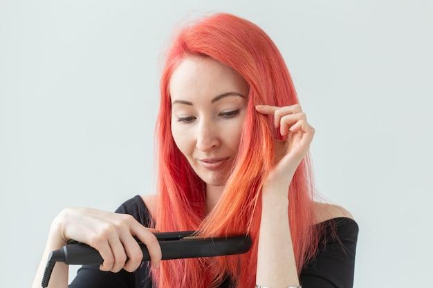 Conceito de estilo de cabelo, cabeleireiro e pessoas - elegante mulher ruiva com chapinha na parede branca.