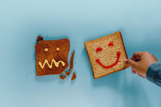 Conceito de estilo de vida de felicidade. flat lay de fatias de pão torrado. pessoa escolheu uma peça bem feita com sorriso no rosto. o queimado com crazy face não é select. vista do topo