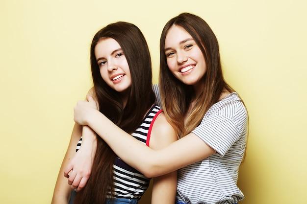 Conceito de estilo de vida e as pessoas: duas jovens amigas juntas e se divertindo. olhando para a câmera. fundo amarelo.