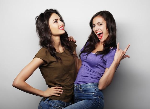 Conceito de estilo de vida e as pessoas: duas jovens amigas juntas e se divertindo. olhando para a câmera.