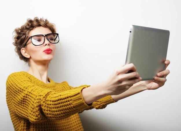 Conceito de estilo de vida e pessoas: mulher feliz tirando uma selfie com tablet digital