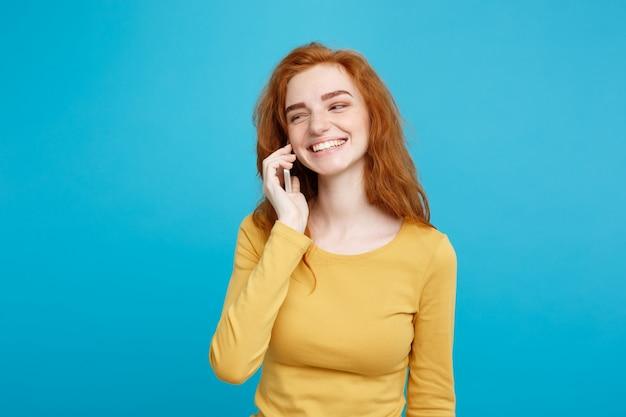 Conceito de estilo de vida e tecnologia - retrato de alegria feliz gengibre cabelo vermelho com alegria e emocionante conversando com amigo por telefone celular. isolado no fundo pastel azul. copie o espaço.