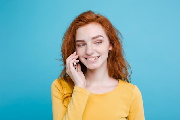 Conceito de estilo de vida e tecnologia - retrato de cheerful feliz ginger vermelho cabelo menina com alegre e emocionante conversando com amigo por telefone celular. isolado no fundo do pastel azul. copie o espaço.