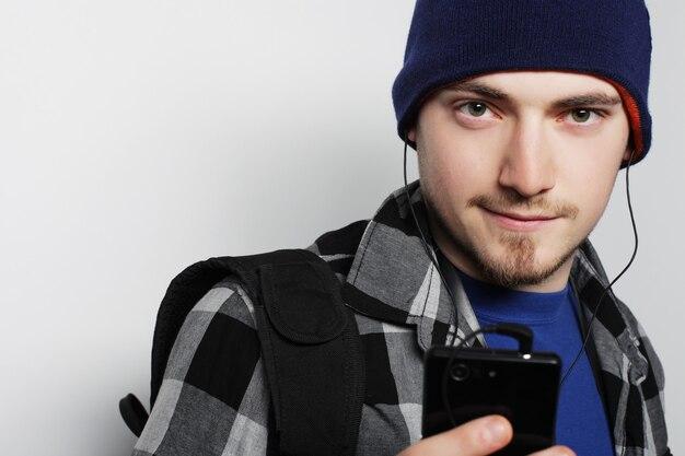 Conceito de estilo de vida, educação e pessoas: jovem ouvindo música e usando o smartphone, em pé contra um fundo cinza.