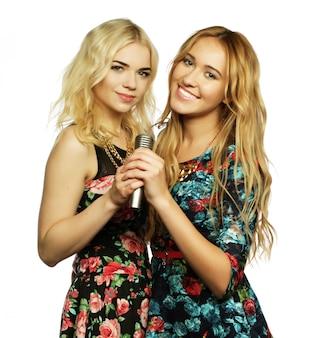 Conceito de estilo de vida, felicidade, emoção e pessoas: duas belas garotas com um microfone cantando e se divertindo