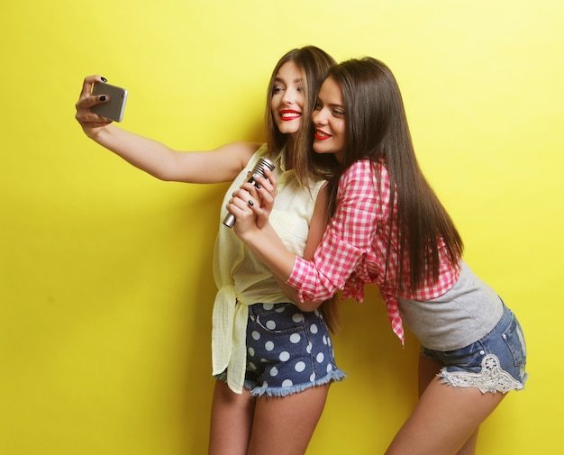 Conceito de estilo de vida, felicidade, emoção e pessoas: duas garotas bonitas e bonitas com um microfone tirando selfie sobre fundo amarelo