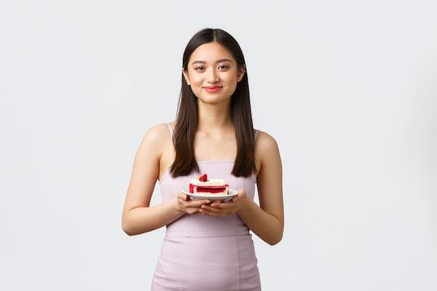 Conceito de estilo de vida, feriados, celebração e comida. linda garota asiática em um vestido de noite, desfrutando de comer um bolo doce e delicioso