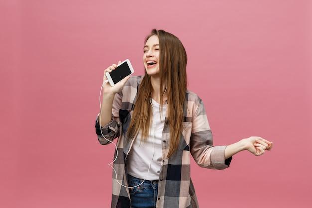 Conceito de estilo de vida. jovem mulher usando telefone para ouvir música no fundo rosa