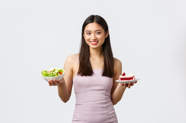 Conceito de estilo de vida, lazer e alimentação saudável. menina asiática bonita alegre em vestido mostrando tigela com salada e pedaço de bolo