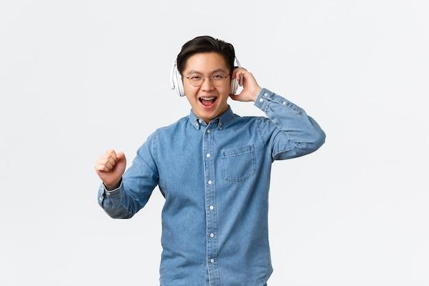 Conceito de estilo de vida, lazer e tecnologia. homem asiático feliz alegre de óculos, dançando despreocupado ao som incrível de música, ótima qualidade de fones de ouvido, usando fone de ouvido sem fio, curtindo a música.