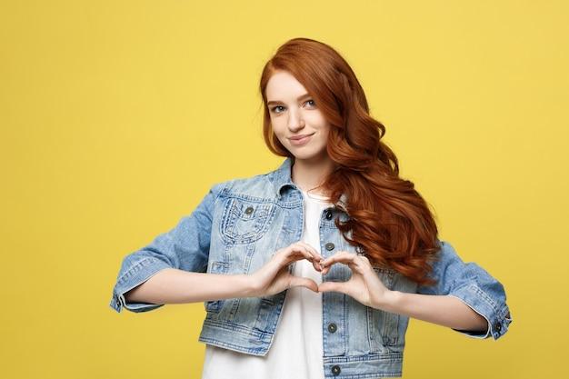 Conceito de estilo de vida: mulher bonita e atraente em jeans fazendo um símbolo de coração com as mãos.