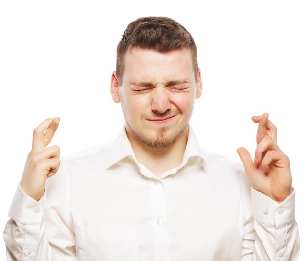 Conceito de estilo de vida, negócios e pessoas: homem de negócios com camisa, mantendo os dedos cruzados em pé contra o espaço em branco