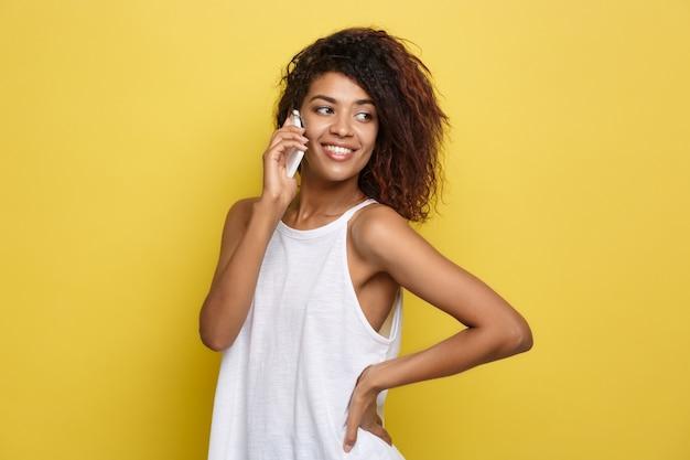 Conceito de estilo de vida - retrato da bela mulher afro-americana alegre conversando no celular com amigo. fundo de estúdio amarelo pastel. espaço de cópia.