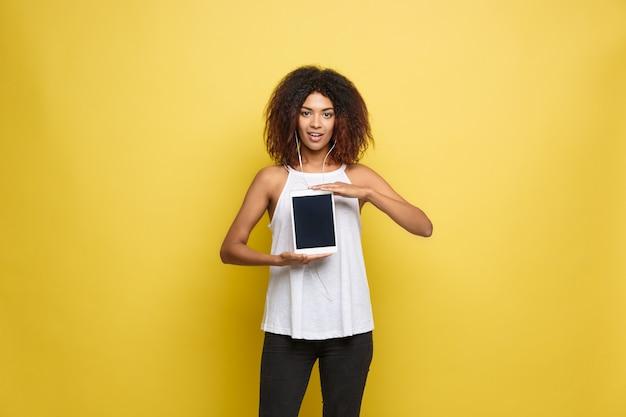 Conceito de estilo de vida - retrato da bela mulher afro-americana alegre jogando algo no tablet eletrônico. fundo de estúdio amarelo pastel. espaço de cópia.