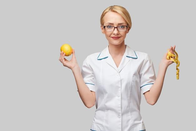 Conceito de estilo de vida saudável do médico nutricionista - segurando frutas de limão orgânico e fita métrica.
