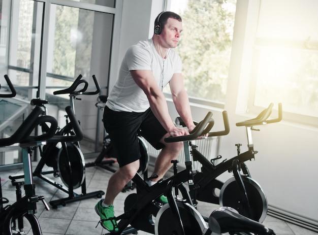 Conceito de estilo de vida saudável. jovem desportivo em t-shirt branca e shorts está exercitando a bicicleta na aula de spinning. treinamento cardíaco