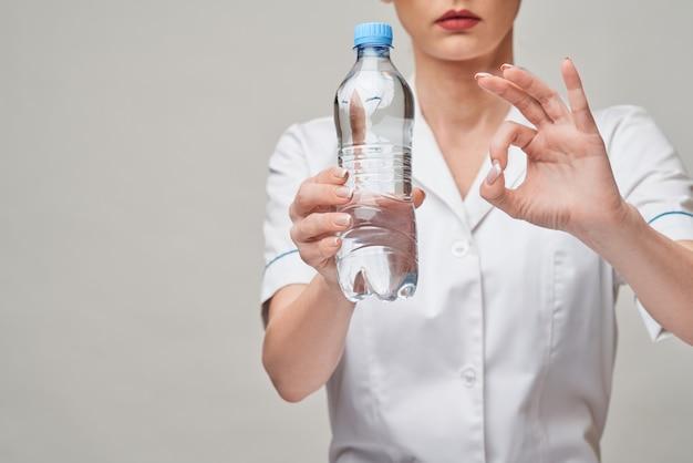 Conceito de estilo de vida saudável nutricionista ou médico nutricionista feminino - segurando uma garrafa de água
