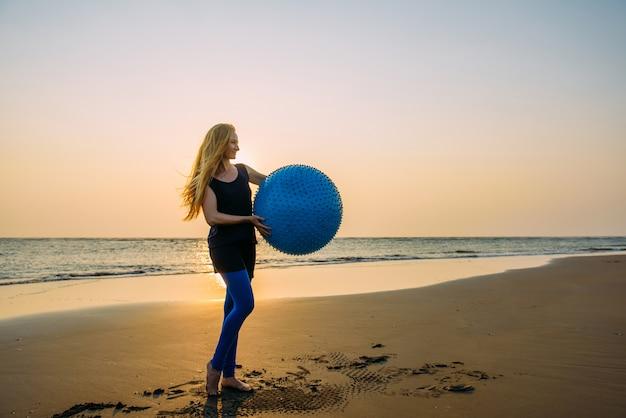 Conceito de estilo de vida saudável para as mulheres. sorrindo jovem fêmea com longos cabelos loiros com grande bola azul no fundo da praia deserta durante o pôr do sol.