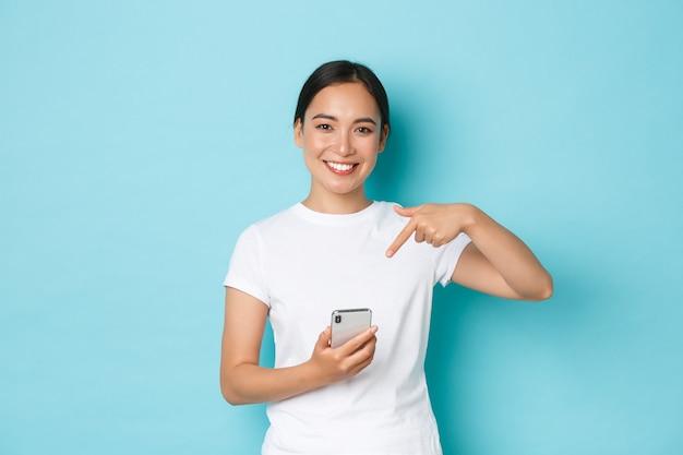 Conceito de estilo de vida, tecnologia e e-commerce. cintura de menina asiática muito sorridente recomenda o aplicativo ou site de compra, usando o telefone celular para pedidos online, apontando o dedo para o smartphone.