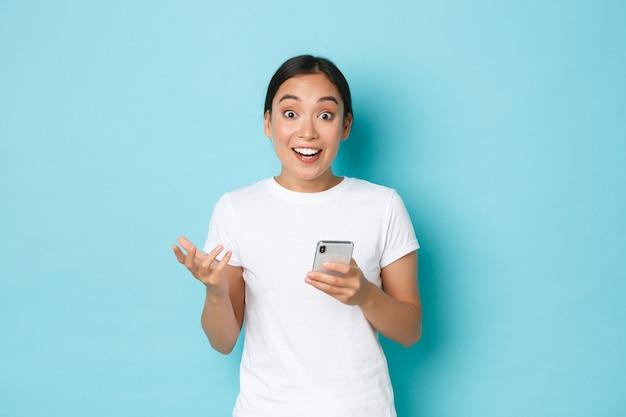 Conceito de estilo de vida, tecnologia e e-commerce. menina asiática feliz surpresa, regozijando-se com o grande anúncio online, parecendo espantada e curiosa, segurando o telefone móvel sobre fundo azul.