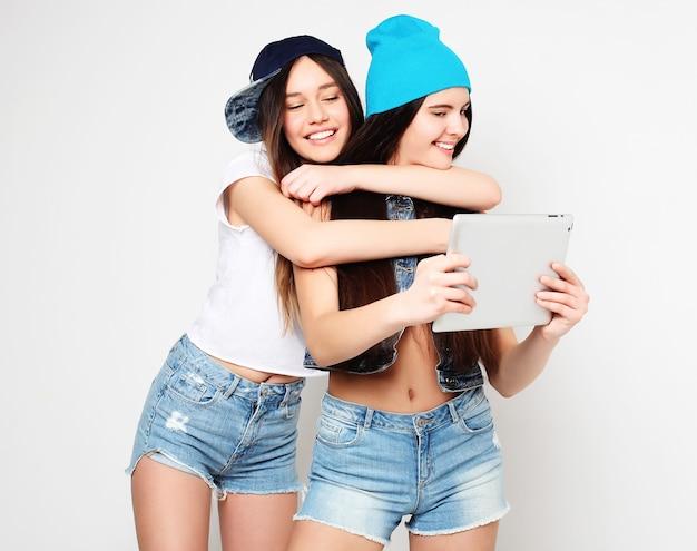 Conceito de estilo de vida, tecnologia e pessoas. garotas felizes com um tablet em branco