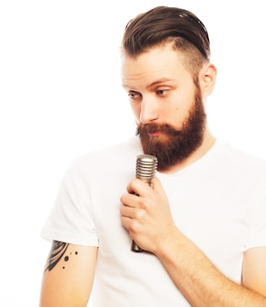Conceito de estilo de vida: um jovem com uma barba, vestindo uma camisa branca, segurando um microfone e cantando. isolado em branco.