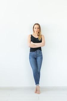 Conceito de estilo e pessoas - jovem de jeans em pé sobre a parede branca e parece sexy.