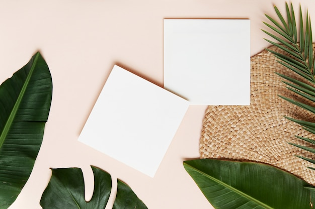 Conceito de estilo flatlay, folha de papel branco e folhas de palmeira tropical na parede rosa