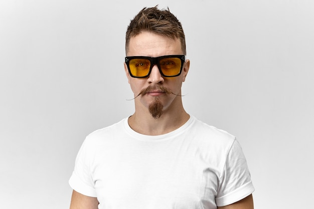 Conceito de estilo, moda e ótica. retrato de bonito na moda jovem caucasiano posando no estúdio vestindo camiseta branca e óculos retangulares amarelos, com olhar sério e confiante