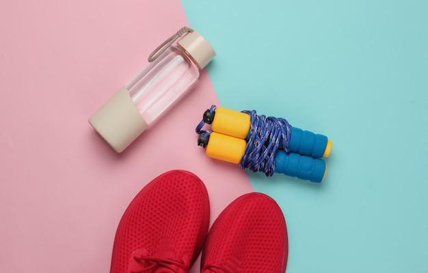 Conceito de estilo plano leigo de estilo de vida saudável, esporte e fitness. tênis para corrida, garrafa de água, pular corda em fundo rosa pastel azul. vista do topo