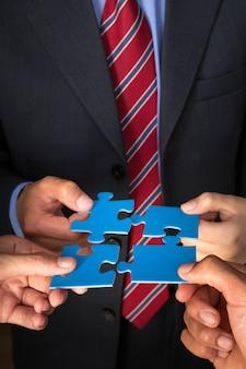 Conceito de estratégia de equipe de negócios. homens com peças de quebra-cabeça