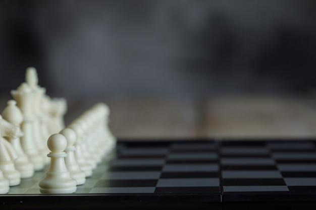 Conceito de estratégia de negócios com o tabuleiro de xadrez com figuras vista lateral.