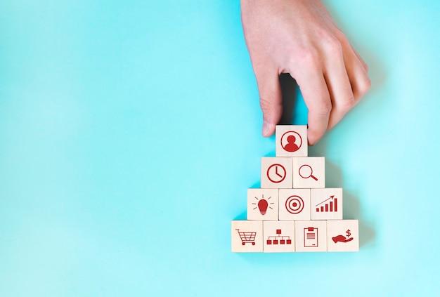Conceito de estratégia de negócios e plano de ação. mão segurando um bloco de cubos de madeira empilhado com ícone