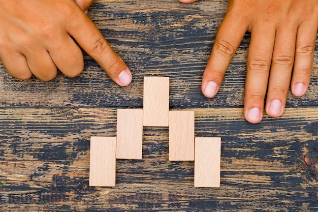 Conceito de estratégia de negócios na configuração plana de fundo de madeira. dedo apontando para o bloco de madeira.
