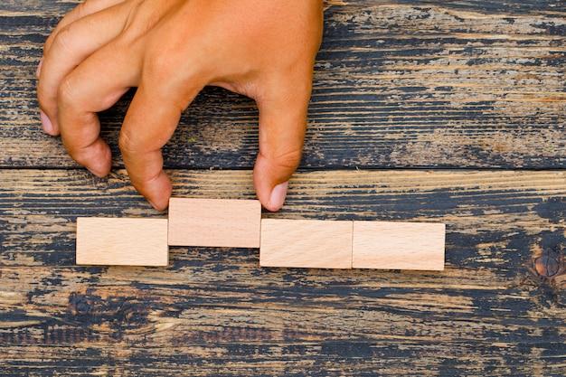 Conceito de estratégia de negócios na configuração plana de fundo de madeira. mão puxando o bloco de madeira.