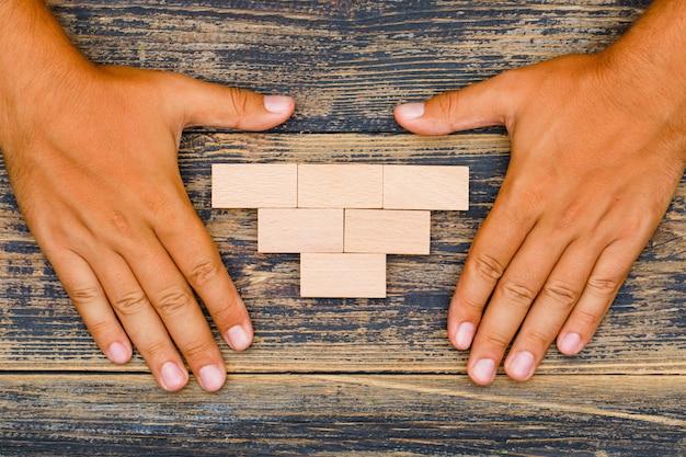 Conceito de estratégia de negócios na configuração plana de fundo de madeira. mãos protegendo blocos de madeira.