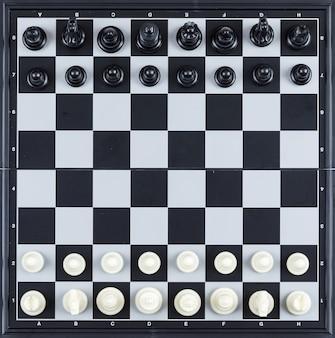 Conceito de estratégia e xadrez com figuras de xadrez na vista superior do tabuleiro de damas.