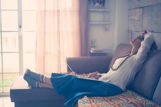 Conceito de estresse e cansaço com uma mulher caucasiana em casa com um laptop pessoal nas pernas