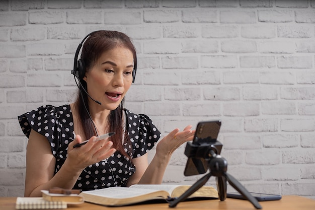 Conceito de estudo da bíblia. mulher asiática ensinando e lendo a bíblia usando um telefone inteligente.