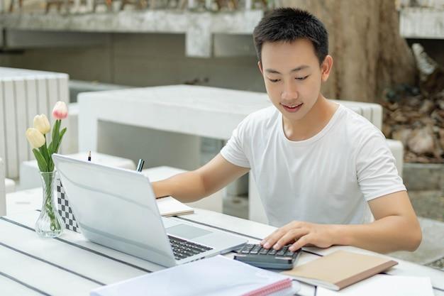 Conceito de estudo on-line, um estudante do sexo masculino em uma camiseta branca, desfrutando de estudar on-line e sentado na frente de seu novo laptop branco ao ar livre.