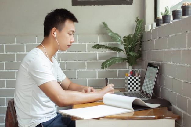 Conceito de estudo online - o estudante do ensino médio ouvindo música com seus fones de ouvido e usando seu laptop para pesquisar informações sobre sua lição de casa no papel.