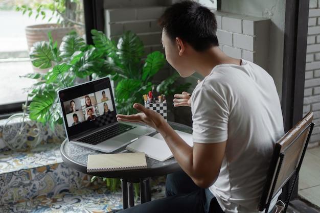 Conceito de estudo online - o estudante universitário que tenta explicar a sua opinião sobre o assunto que conclui no caderno enquanto os seus colegas o ouvem.