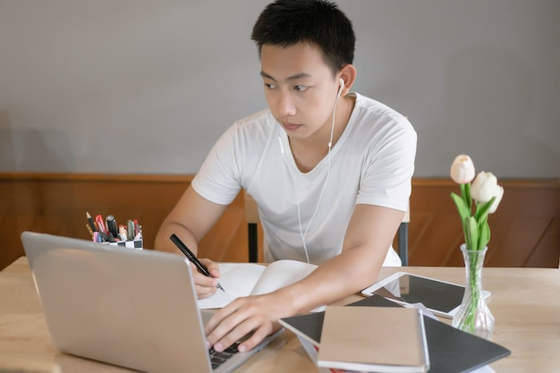 Conceito de estudo online: o homem clássico de camiseta branca está ocupado tentando terminar seus projetos, o que bagunça sua mesa com ipad, laptop e livros.