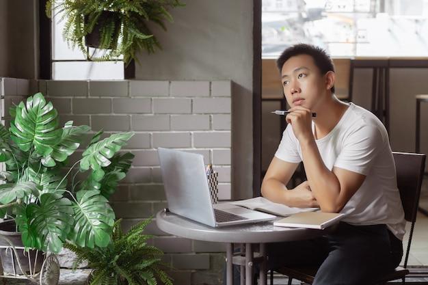 Conceito de estudo online o jovem de camiseta branca simples sendo atencioso e sério na frente da tela durante a aula online.