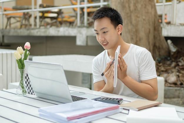 Conceito de estudo online, o jovem homem apresentando seu novo conceito do projeto para seu professor, mostrando seu plano em um pequeno livro através de seu laptop.