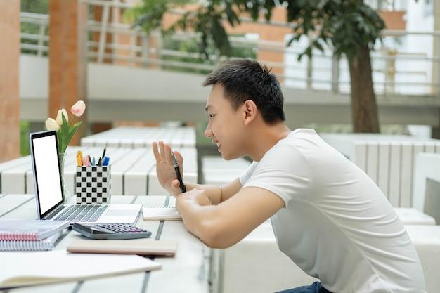 Conceito de estudo online: um aluno do sexo masculino que estuda em uma sala de aula online usando seu novo laptop branco, levantando a mão esquerda para fazer algumas perguntas ao professor.