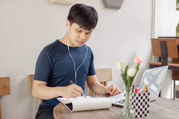 Conceito de estudo online: um estudante de cabelos negros fazendo sua lição de casa pesquisando informações na internet e usando esta caneta preta para escrever a conclusão de sua pesquisa no papel.