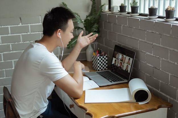 Conceito de estudo online um jovem estudante de camiseta branca sentado na esquina de um café e dando foco em responder a pergunta do professor na aula online.